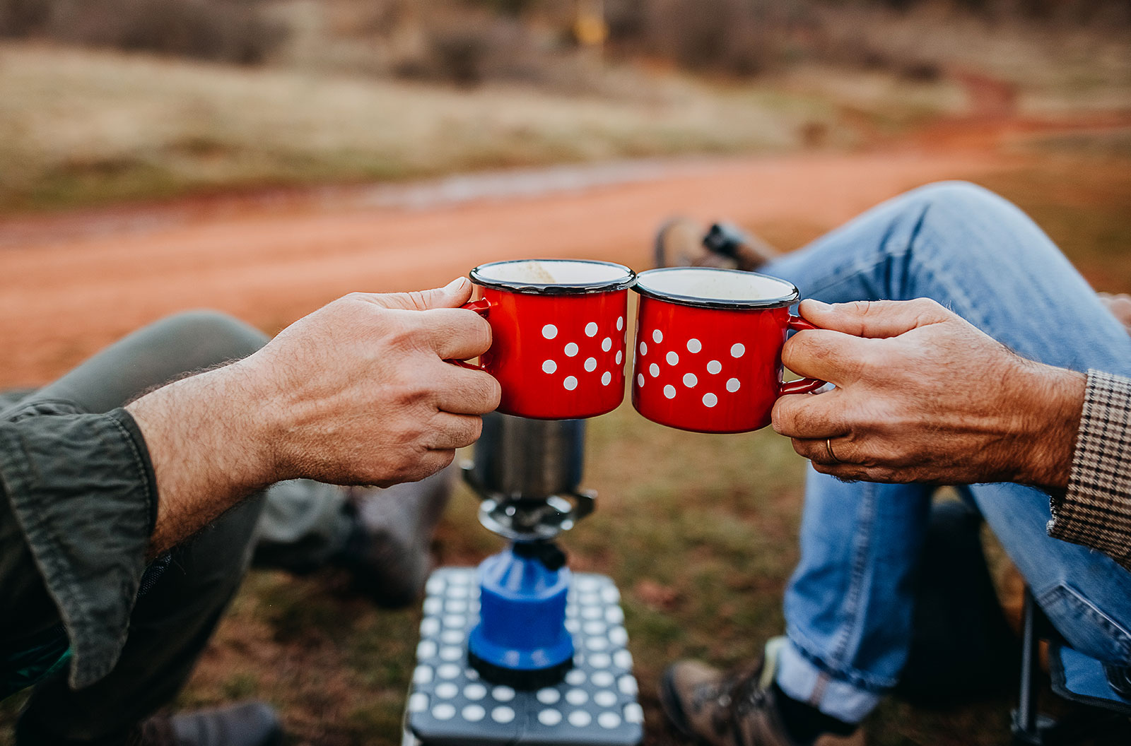 Two people sitting down and toasting their tin cups of coffee while camping