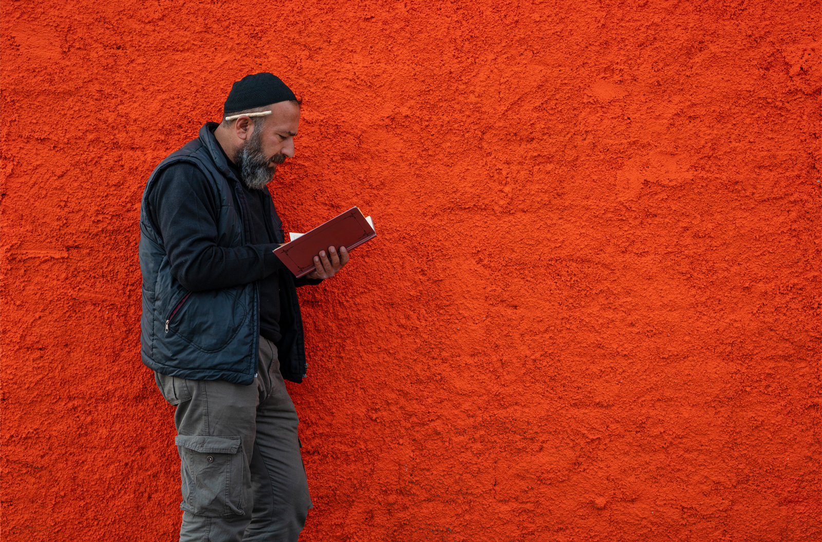 Bearded man reading a book while leaning up against a textured orange wall