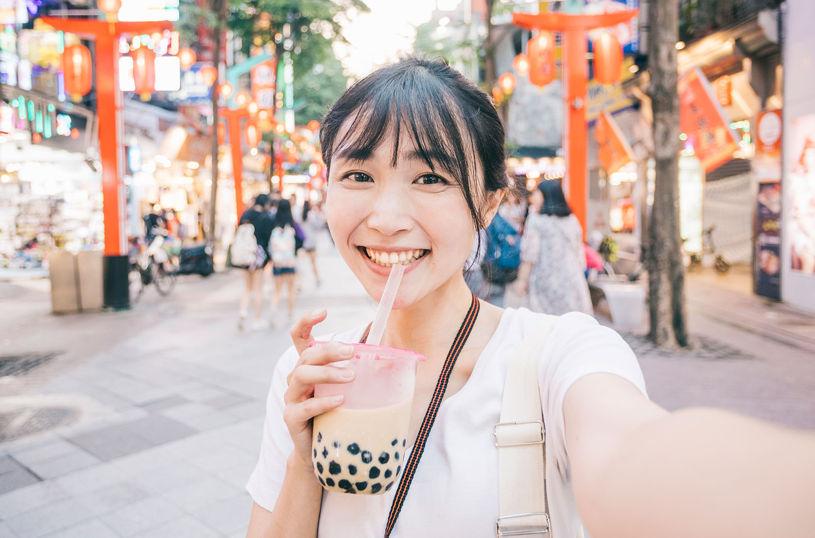 Young woman taking a selfie while drinking bubble tea